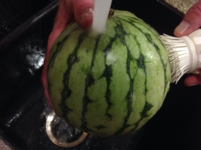 Washing a watermelon under cool running water with a clean scrub brush